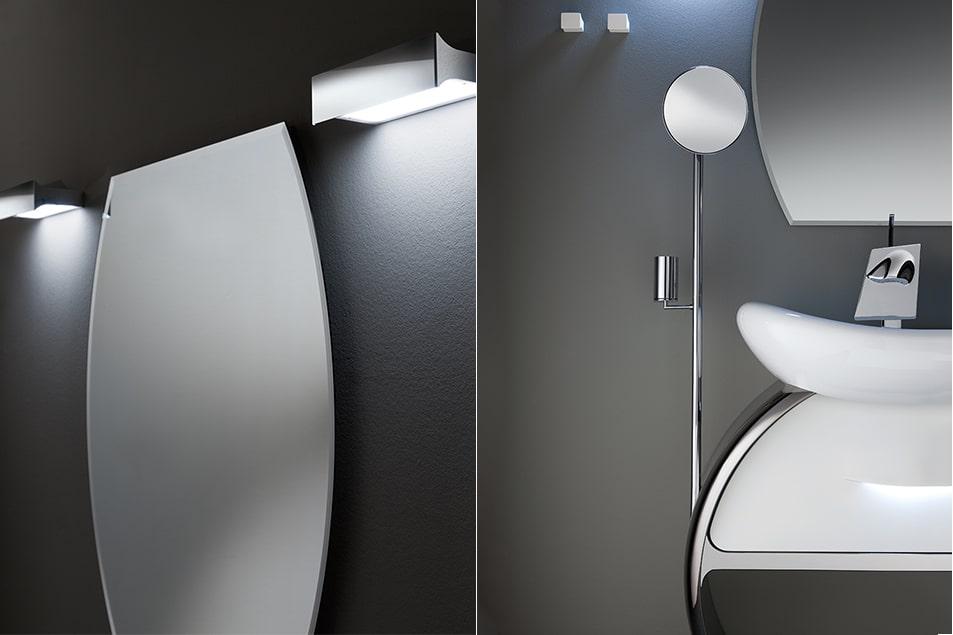 Lo specchio sopra il lavabo e quello accostato alla colonna contenitiva seguono le linee sinuose del mobile.