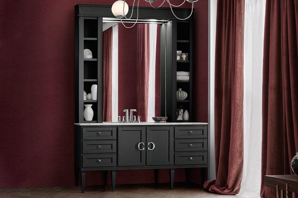 Mobile bagno Cerasa con piedini alti, ante e cassetti, e pensili con elementi a giorno che incorniciano un ampio specchio
